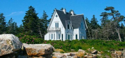 Great Duck Island House | View from shoreline and through field of flowers of the house exterior